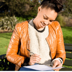 Happy women sitting on a park bench in an orange leather jacket and white sweater holding a pen and looking at a piece of paper on her lap