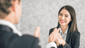 Women smiling while man congratulatorily claps in front of her