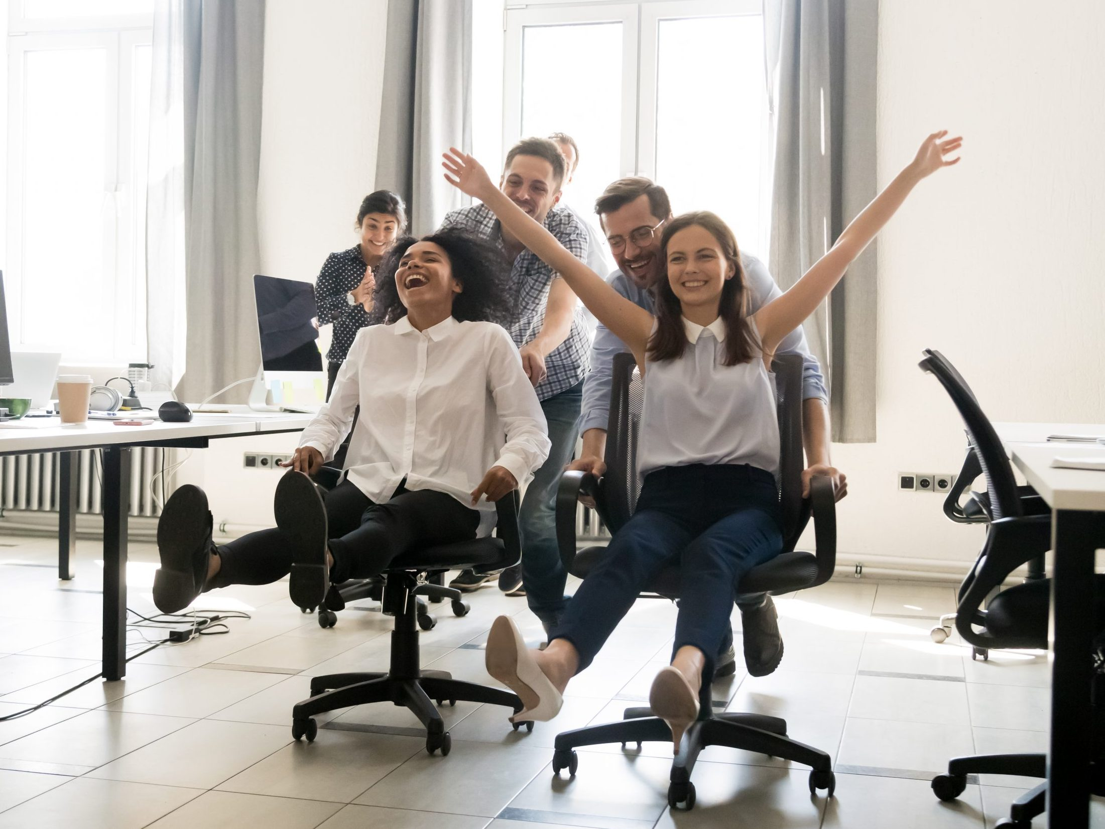 Happy,Multiracial,Colleagues,Group,Having,Fun,Together,,Riding,On,Chairs
