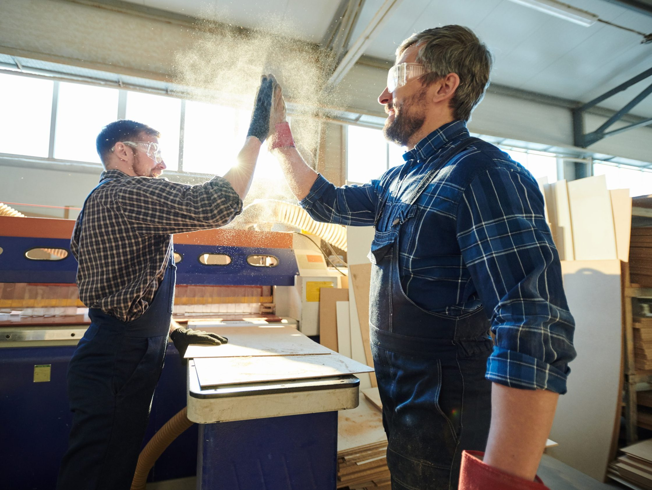 Positive,Satisfied,Bearded,Factory,Workers,Standing,At,Workbench,With,Particleboard