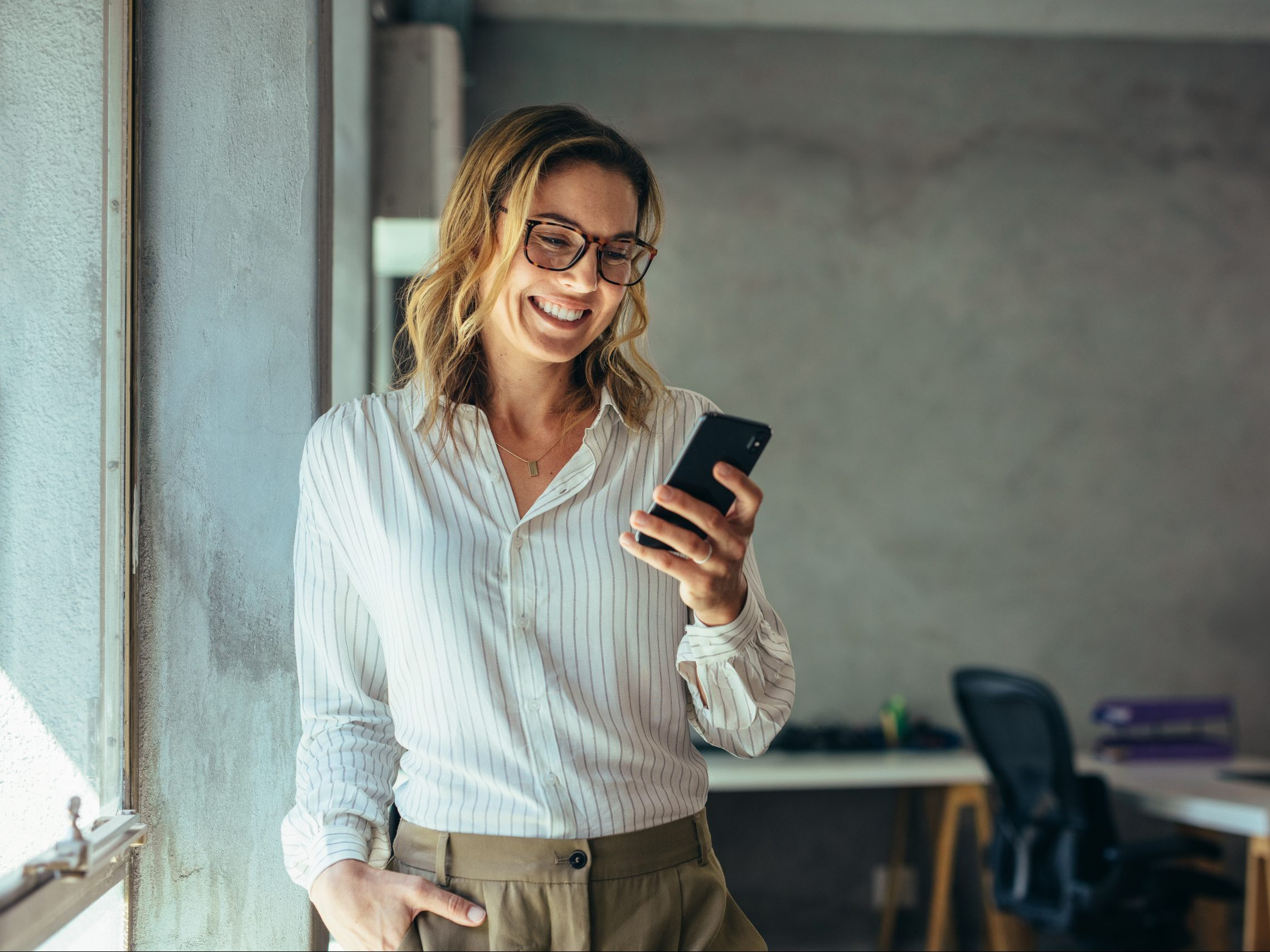 Smiling,Businesswoman,Using,Phone,In,Office.,Small,Business,Entrepreneur,Looking