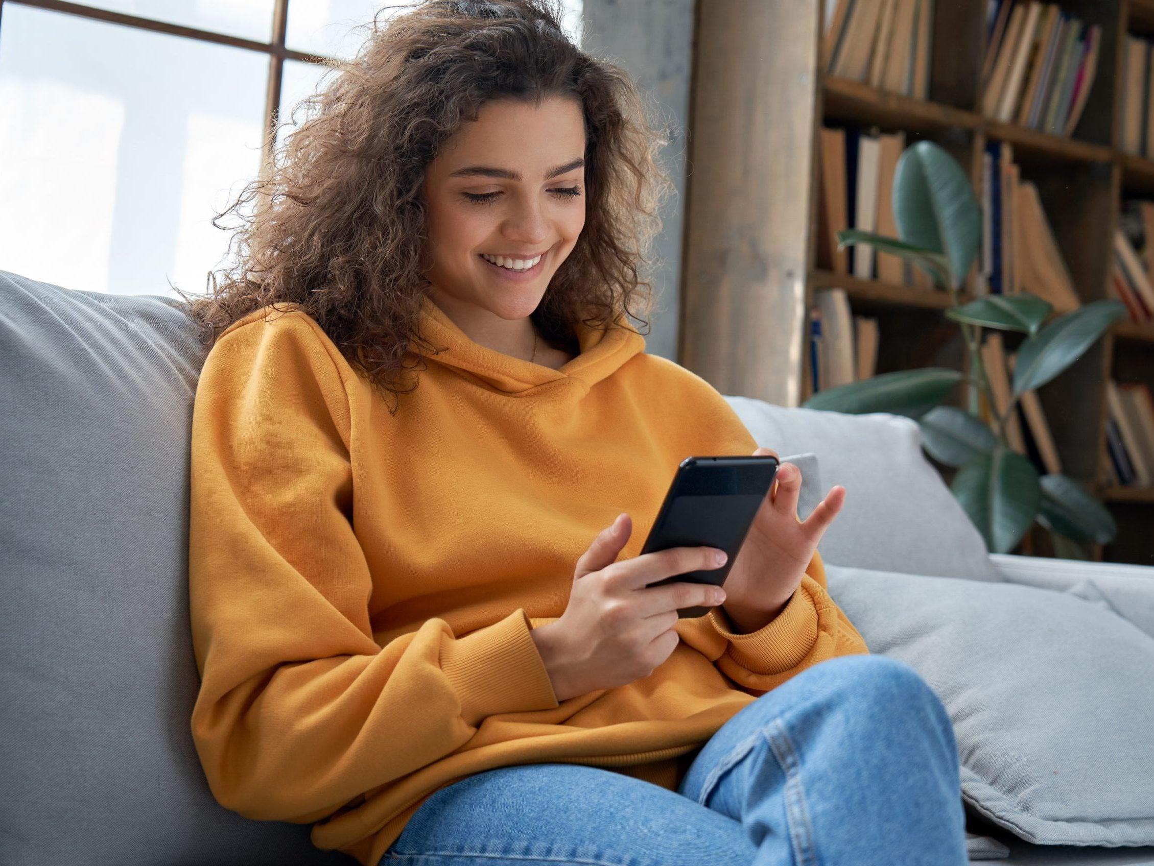 Happy,Millennial,Hispanic,Teen,Girl,Checking,Social,Media,Holding,Smartphone