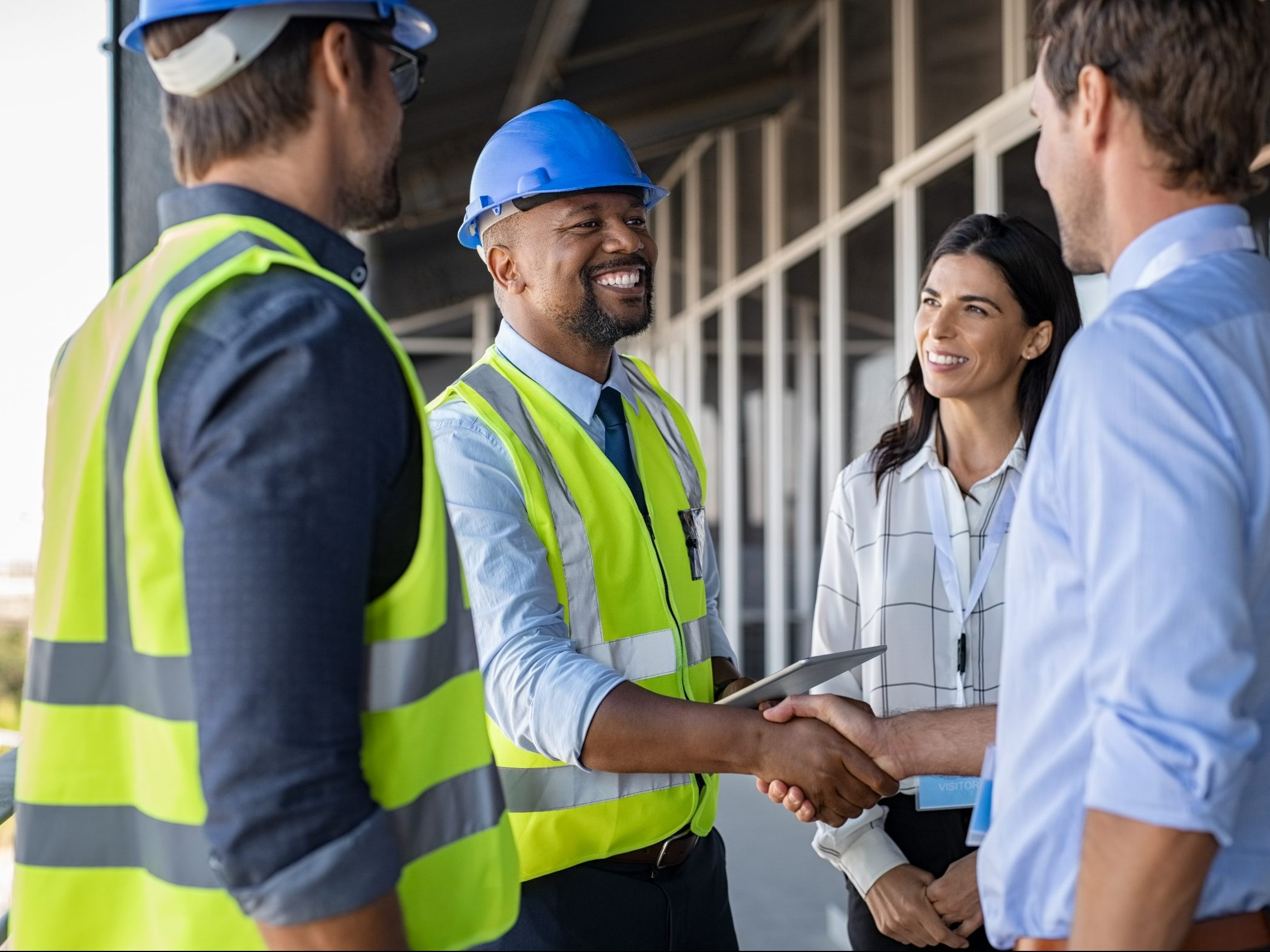 Smiling,Engineer,Shaking,Hands,At,Construction,Site,With,Happy,Architect.