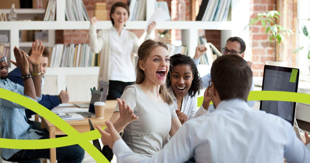 Office setting of excited people clapping and cheering for a fellow employee
